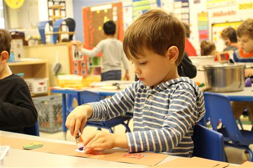 Preschool student putting glue on paper